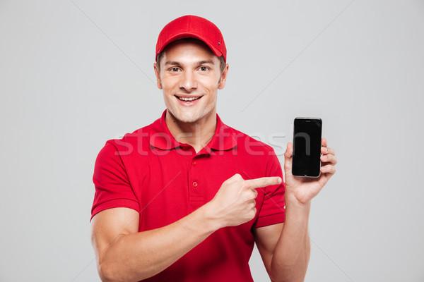 счастливым курьер телефон глядя камеры изолированный Сток-фото © deandrobot