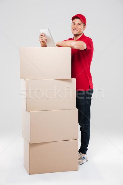 улыбаясь за коробки изолированный серый Сток-фото © deandrobot