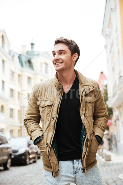Cheerful young man walking on the street and looking aside. Stock photo © deandrobot