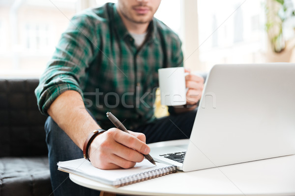 Cropped image of man with laptop on sofa Stock photo © deandrobot