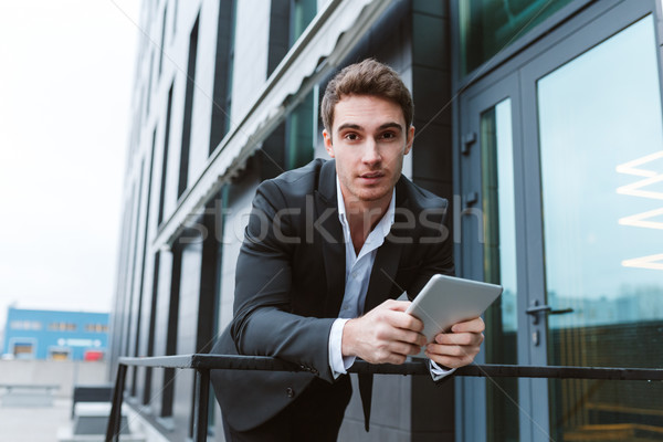 Stock photo: Business man standing with laptop computer