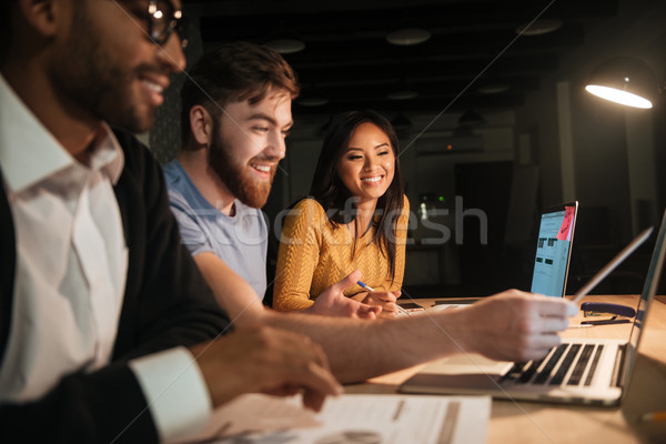Group of colleagues working at night in office with laptop Stock photo © deandrobot
