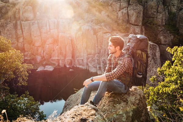 冒險 男子 坐在 岩 側面圖 商業照片 © deandrobot