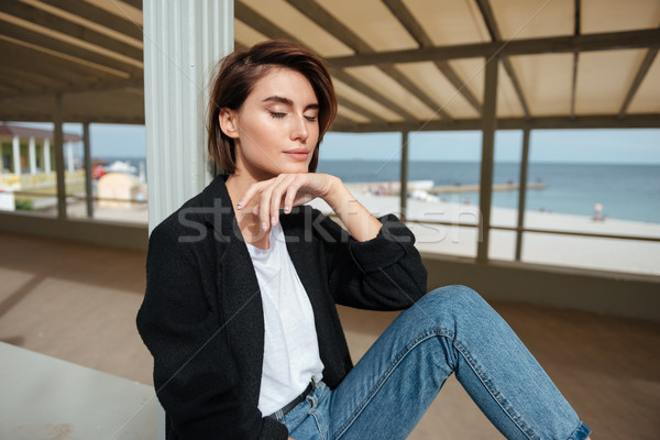 Woman sitting with eyes closed in verandah near the sea Stock photo © deandrobot