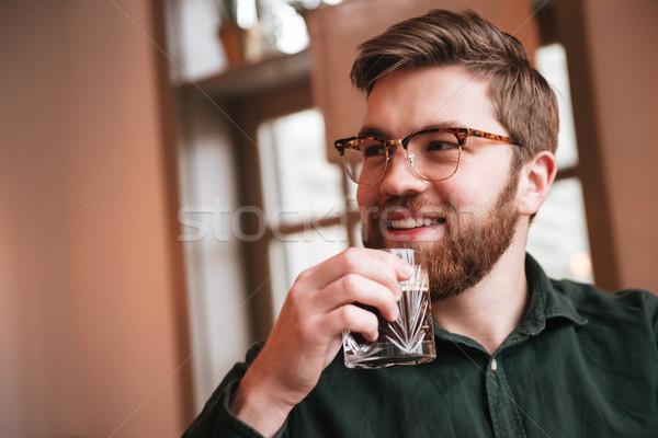 Vonzó szakállas fiatalember iszik whiskey kép Stock fotó © deandrobot