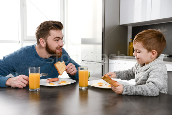 Happy young father eating at kitchen with little son Stock photo © deandrobot