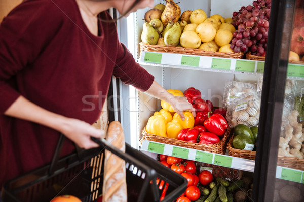 Woman choosing and buying bell pepper in supermarket Stock photo © deandrobot