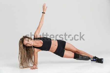 Smiling beautiful young sportswoman lying and doing exercises Stock photo © deandrobot