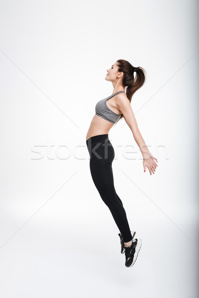 Stock photo: Portrait of young brunette sports woman jumping and looking away