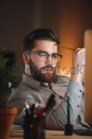 Concentrated web designer working late at night in office Stock photo © deandrobot