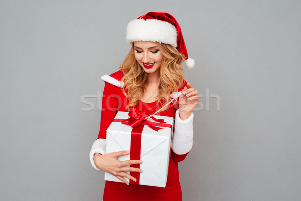 Beautiful blonde woman in red xmas outfit opening her present Stock photo © deandrobot