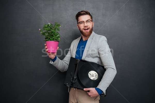Smiling bearded young businessman holding flowers in pot and turntable Stock photo © deandrobot
