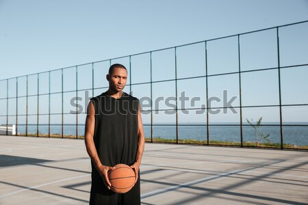 Yuong afro american sportsman holding basketball and looking away Stock photo © deandrobot