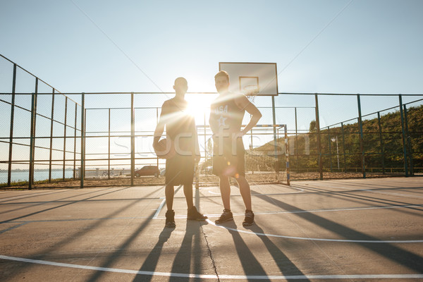 Sportsmen standing with basketball at the playgroung Stock photo © deandrobot