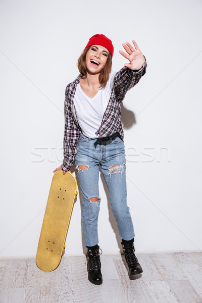 Woman isolated over white background holding skateboard Stock photo © deandrobot