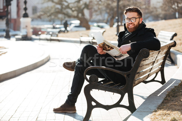 Stock photo: Cheerful bearded young man reading newspaper on the bench outdoors
