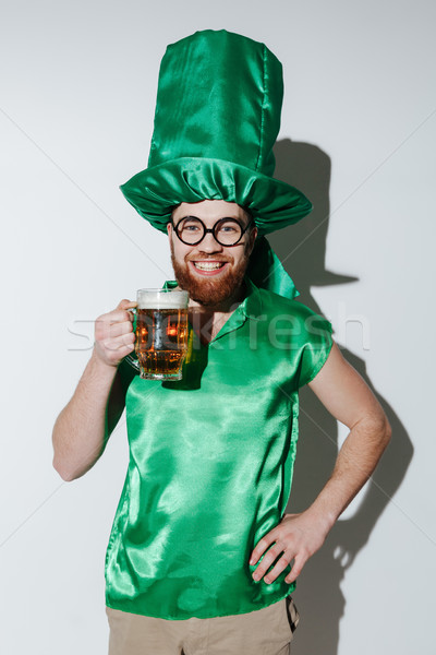 Vertical image of Smiling man in st.patriks costume holding beer Stock photo © deandrobot