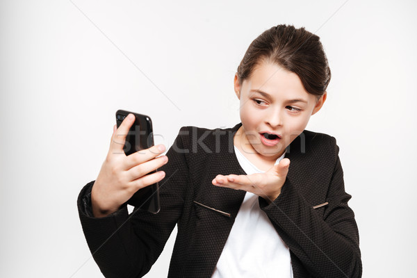 Geschokt jong meisje permanente telefoon afbeelding Stockfoto © deandrobot