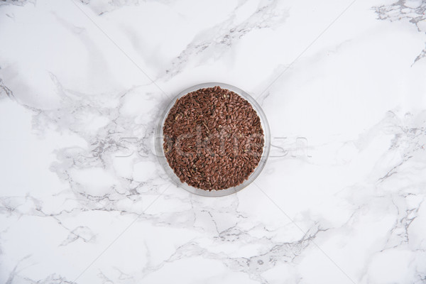 Top view of linen seeds in a bowl Stock photo © deandrobot