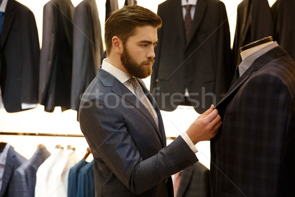 Side view of man choosing a jacket in shop Stock photo © deandrobot