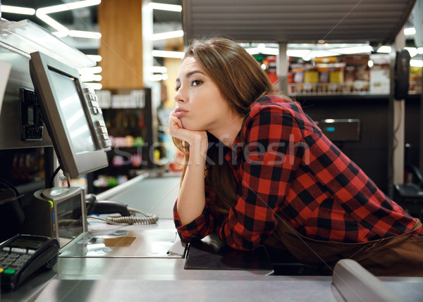 Tired cashier lady lies on workspace in supermarket shop Stock photo © deandrobot