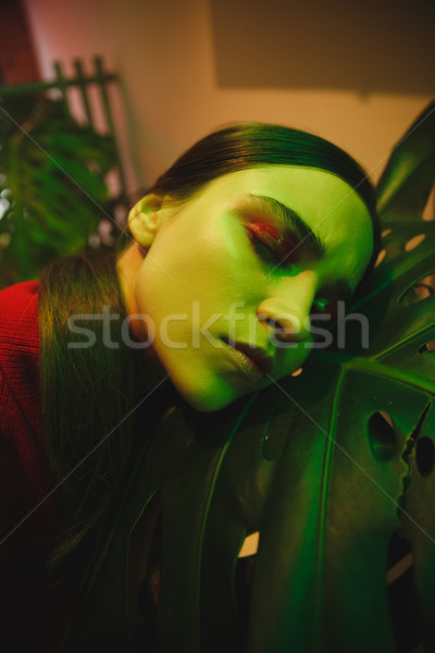 Close up portrait of woman lying on large leaf Stock photo © deandrobot