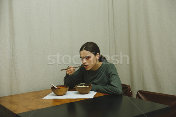 Side view of serious woman eating by the table Stock photo © deandrobot