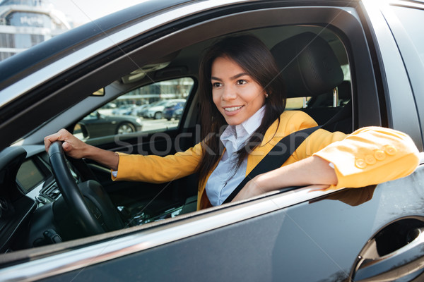 Happy business woman driving her new car Stock photo © deandrobot