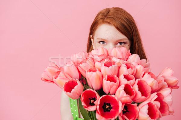 Close up portrait of woman hiding behind bouquet of flowers Stock photo © deandrobot