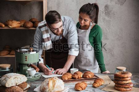 Vertical image of happy bakers in bakery Stock photo © deandrobot