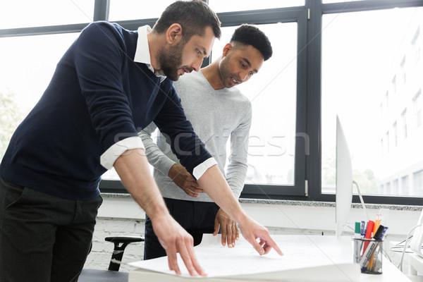 Dos jóvenes masculina los trabajadores de oficina senalando tabla Foto stock © deandrobot