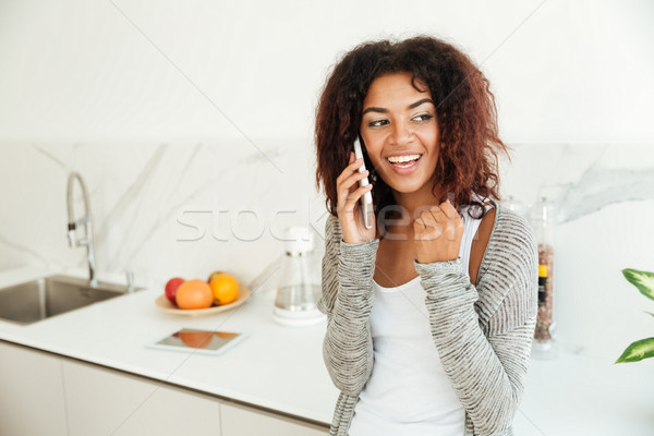 Young woman talking on phone in kitchen Stock photo © deandrobot