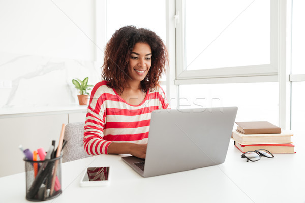 Busy woman in casual clothes working on laptop at home Stock photo © deandrobot