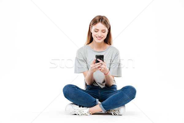 Woman using smartphone and sitting on floor Stock photo © deandrobot