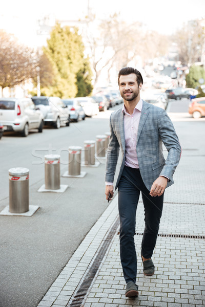 Full length portrait of a smiling handsome man in jacket Stock photo © deandrobot