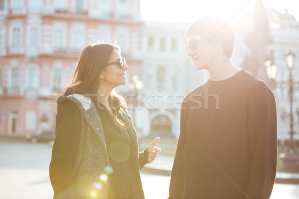 Happy young lady walking outdoors with her brother. Stock photo © deandrobot