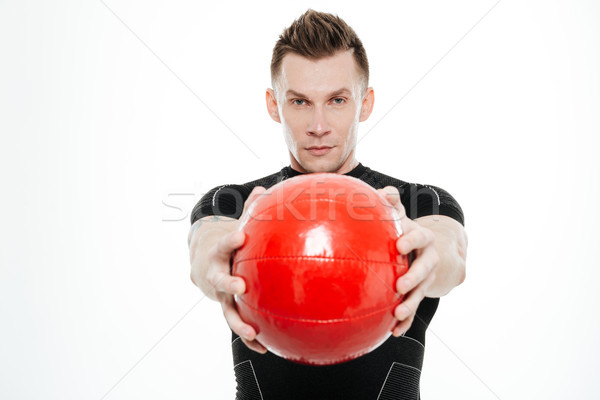 Attractive sportive man doing exercises with heavy fitness ball Stock photo © deandrobot
