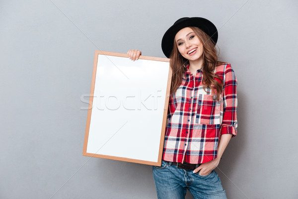 Portrait of a happy smiling young woman in plaid shirt Stock photo © deandrobot