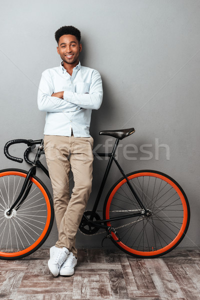 Young african man standing over grey wall with bicycle. Stock photo © deandrobot