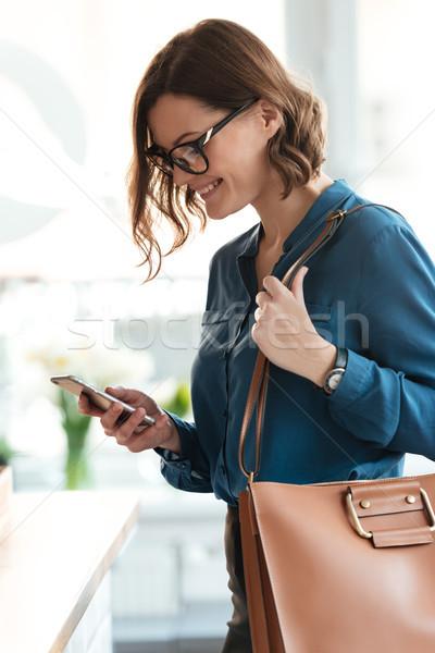 Stock fotó: Oldalnézet · portré · mosolyog · fiatal · nő · szemüveg · mobiltelefon