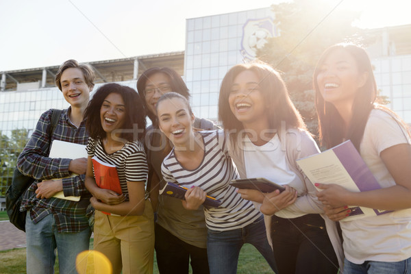 Multiethnic group of young cheerful students standing outdoors Stock photo © deandrobot