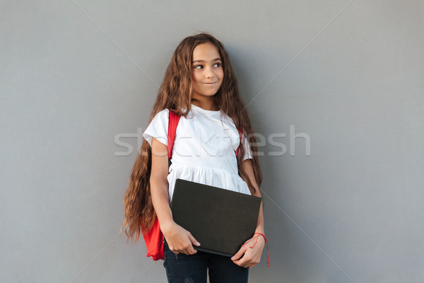 Smiling mystery brunette schoolgirl with long hair hugging book Stock photo © deandrobot