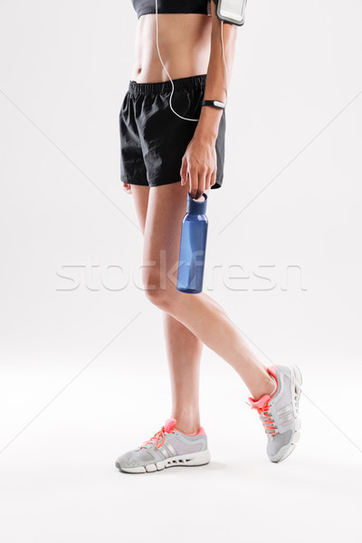 Cropped image of a sportswoman in earphones holding water bottle Stock photo © deandrobot