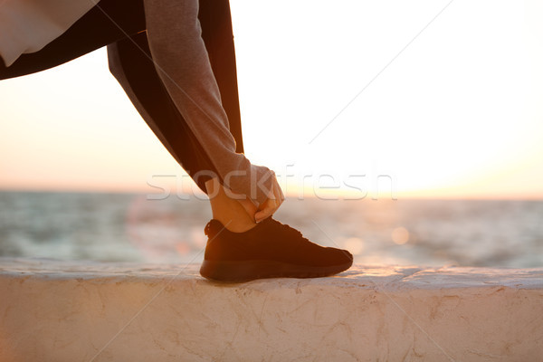 Cropped photo of sport woman tying shoelace at the seaside Stock photo © deandrobot