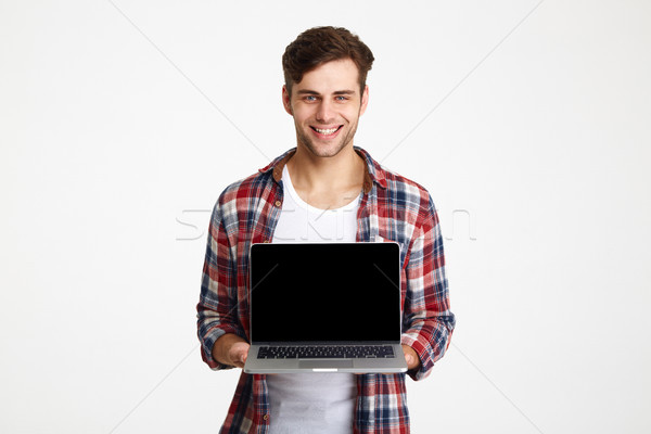 Stock photo: Portrait of a happy cheerful man showing blank screen laptop