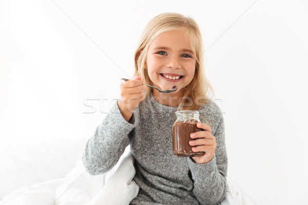 Happy blonde girl in gray pajamas holding glass jar and spoon wi Stock photo © deandrobot