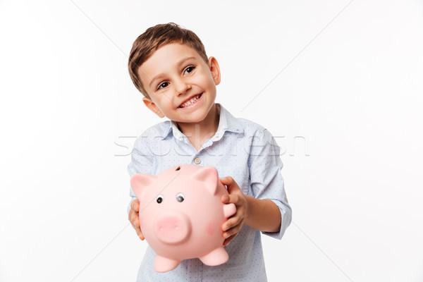 Portrait of a cherry cute little kid holding piggy bank Stock photo © deandrobot