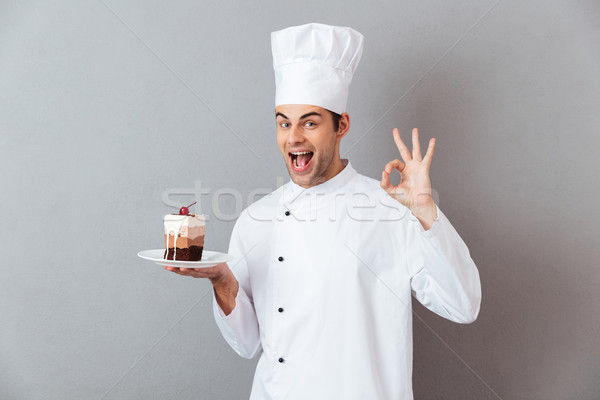 Portrait of a cheery happy male chef dressed in uniform Stock photo © deandrobot