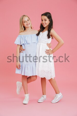 Full length side view portrait of a two joyful girls Stock photo © deandrobot