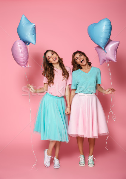Two happy young girls dressed in bright colorful clothes Stock photo © deandrobot